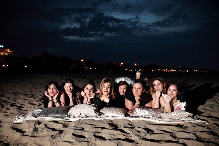 Fotografare eventi, gruppo di ragazze al mare, con lo sfondo delle luci della città