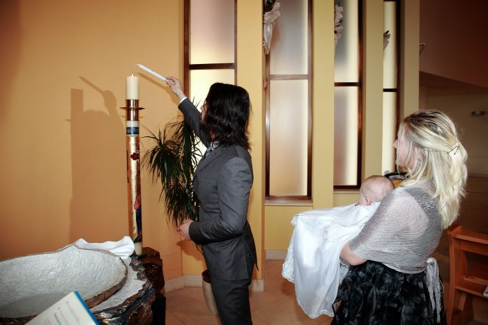 Immagini fotografiche del rito del Battesimo a Giulianova, il padre accende la candela battesimale