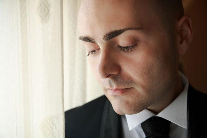 Foto del volto dello sposo con sguardo verso il basso