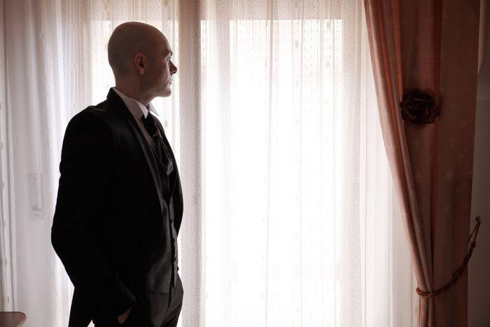 Foto dello sposo di profilo che guarda pensieroso dalla finestra