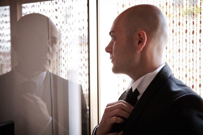 Foto dello sposo a mezzo busto riflesso sulla finestra