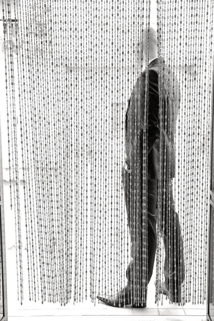 Fotografia in bianco e nero dello sposo a figura intera di spalle nascosto da fili di tenda a figura intera di spalle nascosto