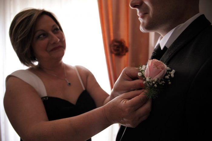 La mamma aggiusta il fiore sull'abito dello sposo
