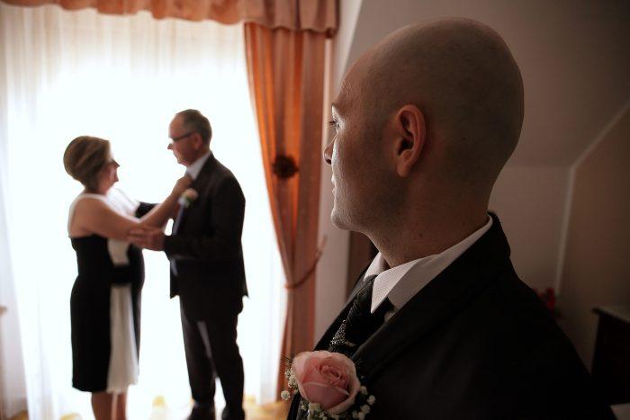 Lo sposo osserva i genitori pronti per la cerimonia nuziale