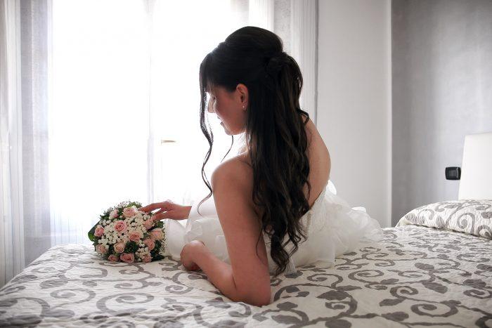 La sposa seduta di spalle sul letto accarezza il bouquet