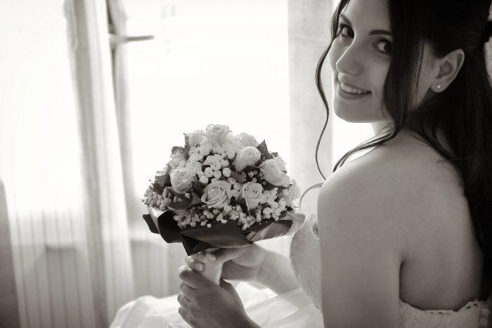 La sposa sorride con un bouquet di fiori tra le mani
