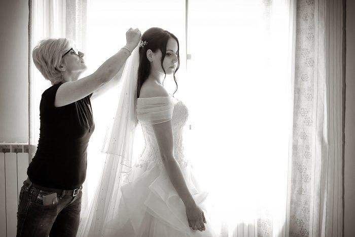 Preparativi al matrimonio: la parrucchiera mette il velo alla sposa