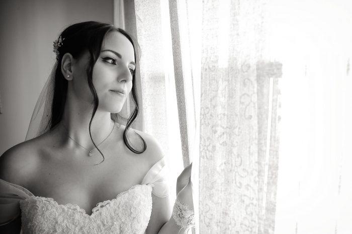 mezzo busto della sposa in bianco e nero che guarda dalla finestra