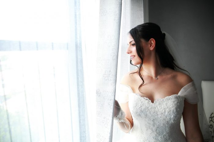 Fotografia della sposa che guarda dalla finestra