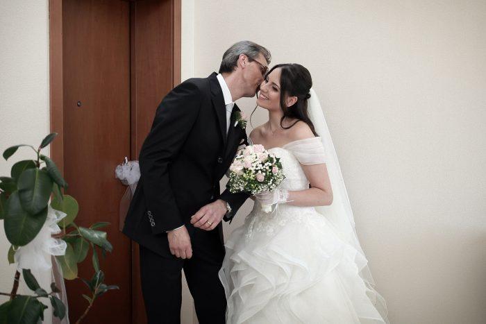 Il padre bacia la sposa sull'uscio di casa