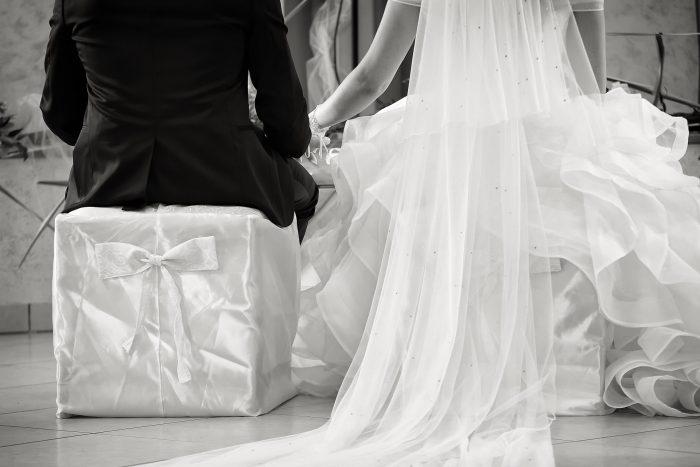 Particolari d'amore in bianco e nero: gli sposi si tengono per mano visti da dietro