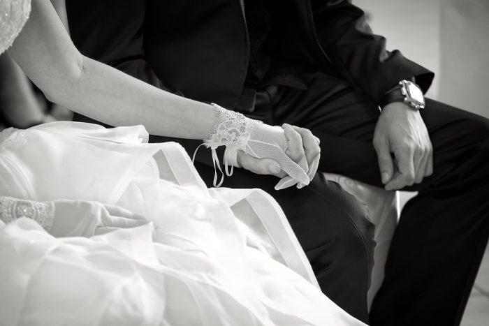 Particolari d'amore in bianco e nero: gli sposi si tengono per mano