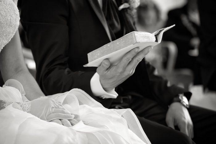 Particolari d'amore in bianco e nero: la mano dello sposo con il libro