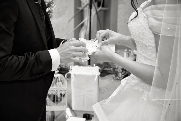 Particolare in bianco e nero: la sposa prende la fede