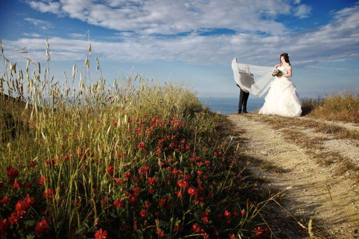 Gli sposi giocano con il velo immersi nei magici colori della natura