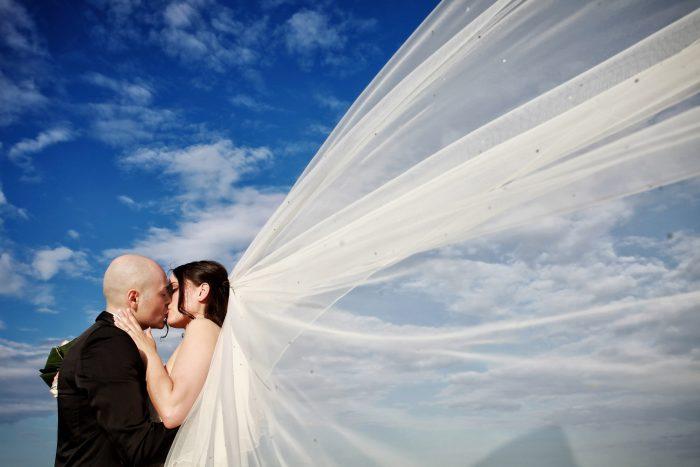 Un bacio appassionato con velo volteggiante nel cielo azzurro