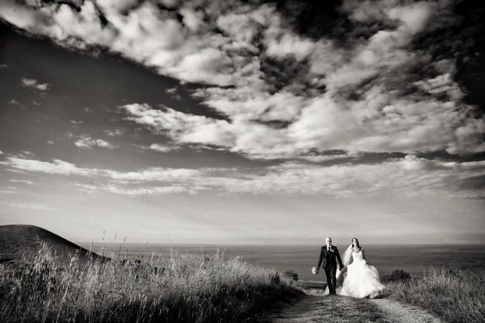 Panoramica in bianco e nero:gli sposi camminano sul sentiero