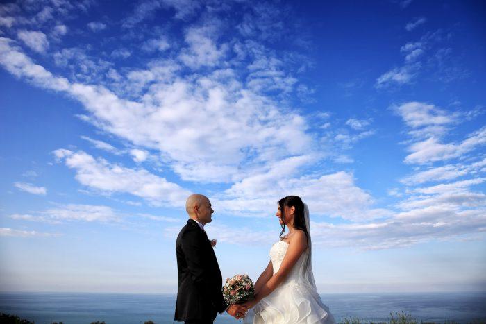 Foto degli sposi che si tengono per mano frontalmente sotto un cielo azzurro con meravigliose nuvole bianche