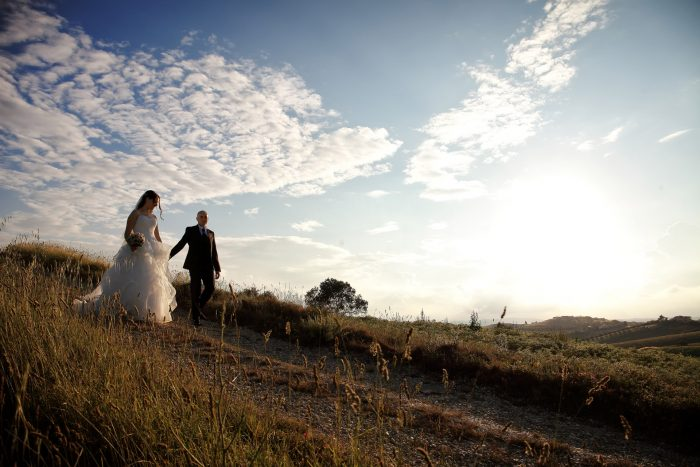 Fotografia panoramica degli sposi che scendono dalla collina mano nella mano