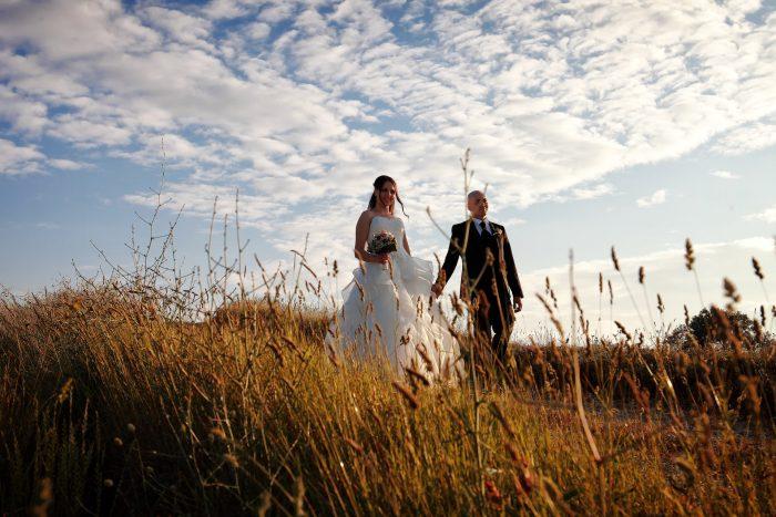 Sposi in cammino tra il grano dorato e un cielo coperto da bianche nuvole
