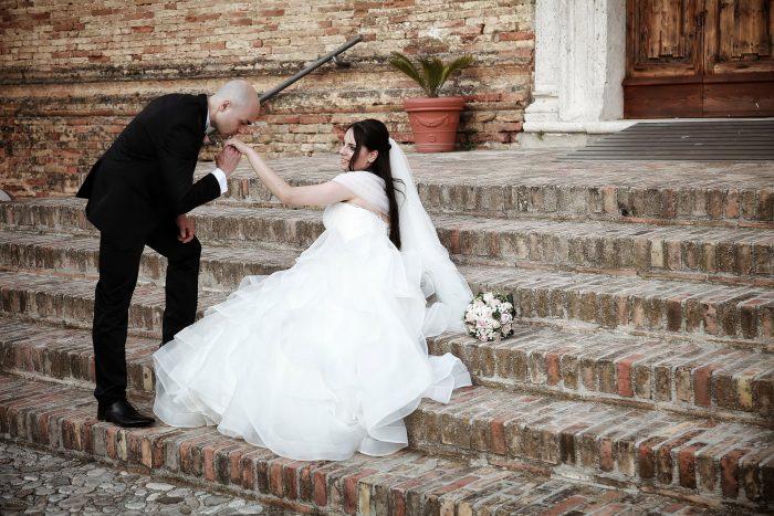 Lo sposo bacia la mano della sposa sulla scalinata della chiesa della Santissima Annunziata a Montepagano