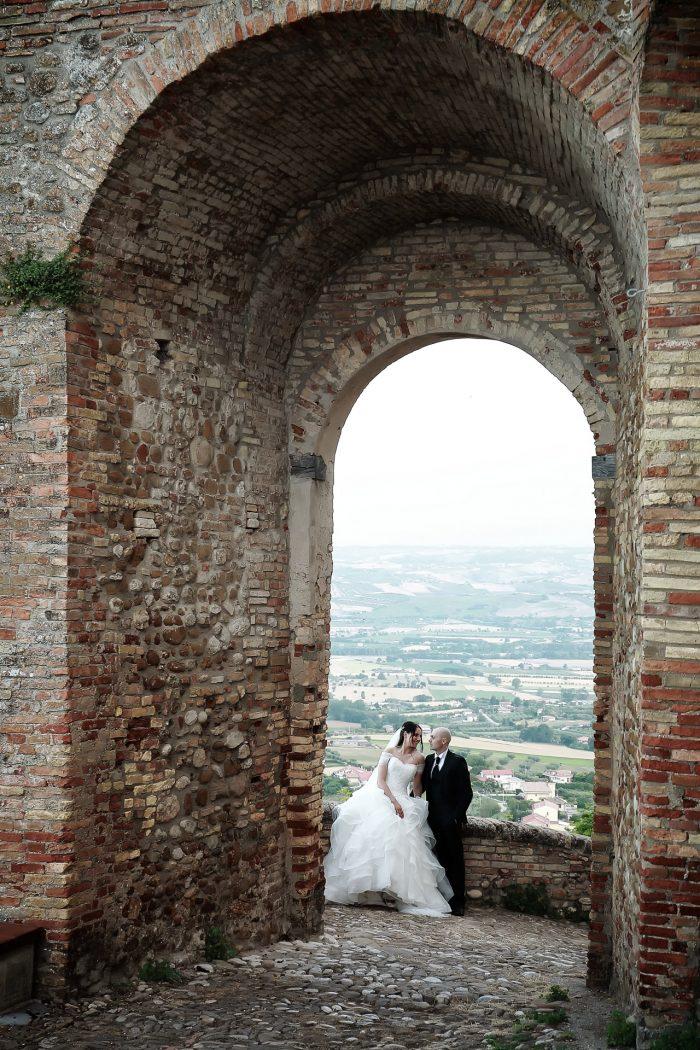 Una prospettiva di archi incornicia gli sposi e le colline abruzzesi sullo sfondo