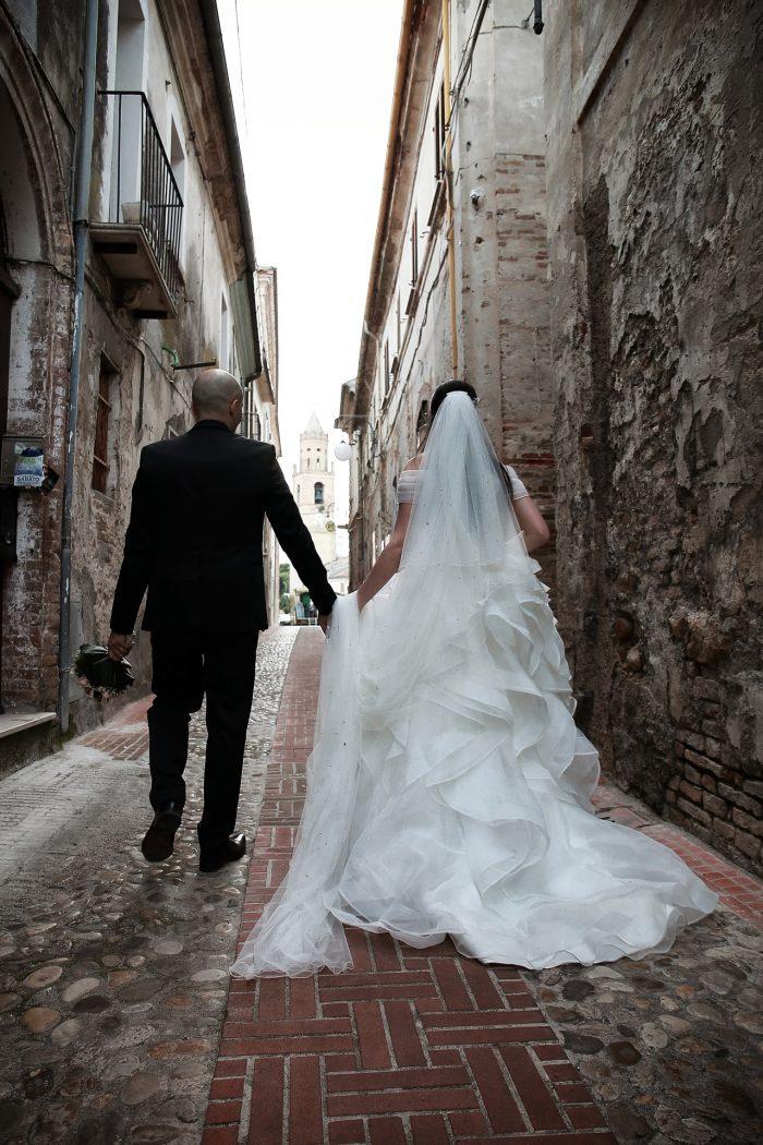 Sposi mano nella mano in cammino verso la Piazza Centrale di Montepagano con il suo monumentale Campanile