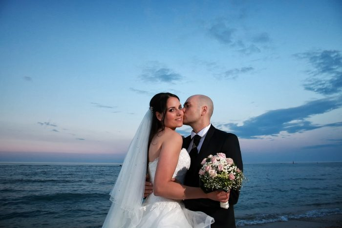 Lo sposo bacia teneramente la sposa sulla guancia