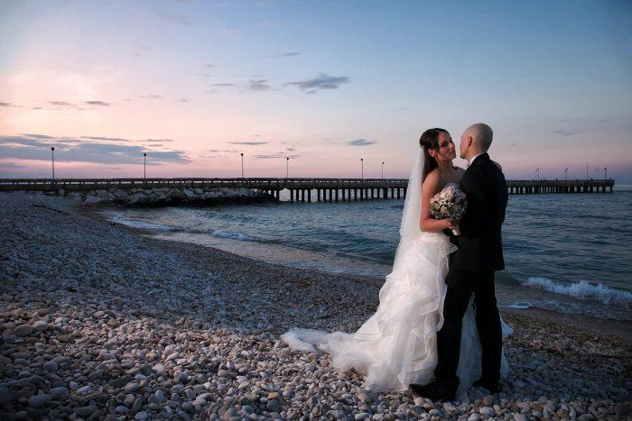 Panoramica del pontile di Roseto degli abruzzi al tramonto con gli sposi che si guardano