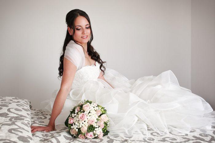Foto frontale della sposa seduta sul letto mentre osserva il bouquet di rose