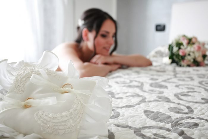 Sposa tra cuscino con fedi nuziali e bouquet