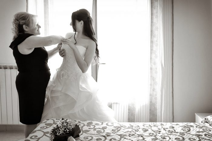 Preparativi al matrimonio: la mamma aggiusta il vestito alla sposa