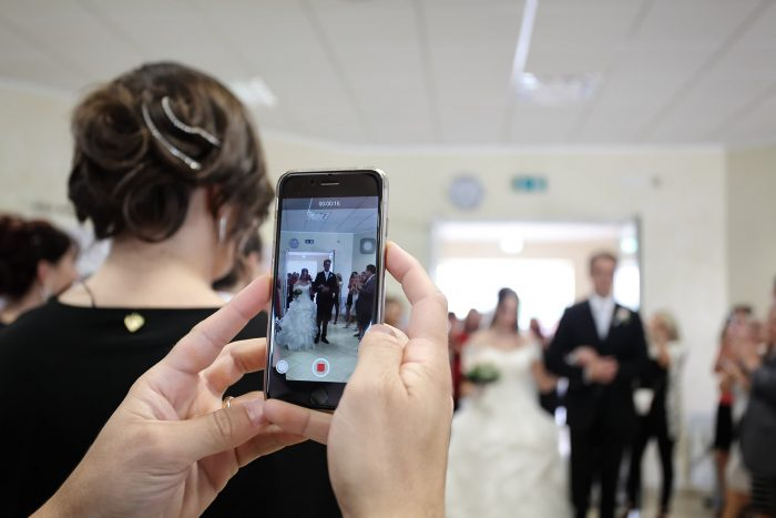 Una prospettiva diversa: ingresso della sposa fotografato attraverso un cellulare