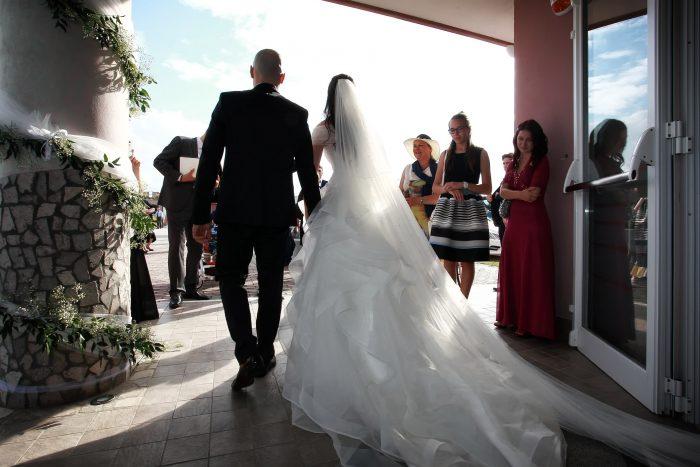 Foto da dietro degli sposi che escono dalla sala al termine del matrimonio