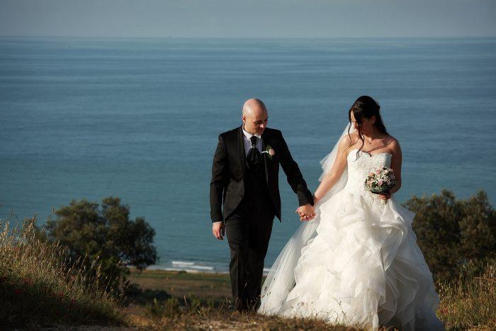 Gli sposi si tengono per mano sulla via del ritorno
