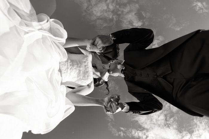 Un bacio in bianco e nero incorniciato da uno scatto ai piedi degli sposi
