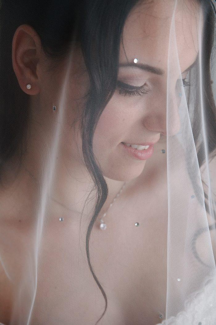 primo piano della sposa coperta dal velo con swarovski