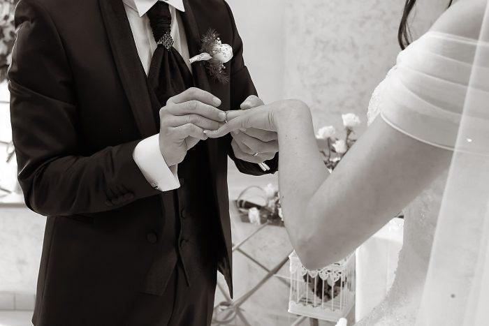 Particolare in bianco e nero: lo sposo mette l'anello alla sposa