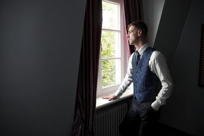 Matrimonio da Favola nella Foresta Nera, sposo alla finestra della suite del Parkhotel Adler a Hinterzarten, in Germania, Hochzeitsfotograf in Deutschland