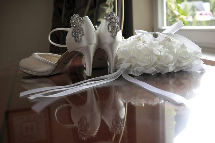Particolari della sposa, le scarpe e il cuscinetto delle fedi
