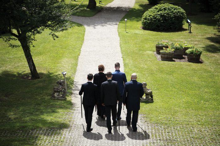 Il giardino del Parkotel Adler a Hinterzarten in Germania, lo sposo, la madre e i tre testimoni in cammino verso l'altare