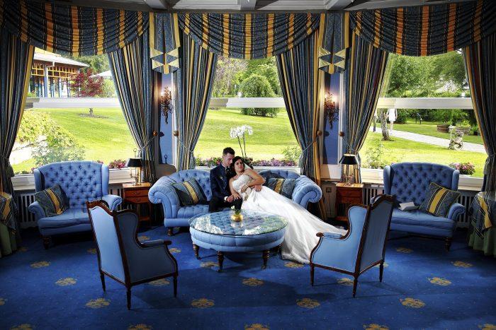 Fairytale wedding in the Black Forest, foto nella hall del Parkhotel Adler a Hinterzarten in Germania, gli sposi si rilassano sul divano, Swiss wedding photographer