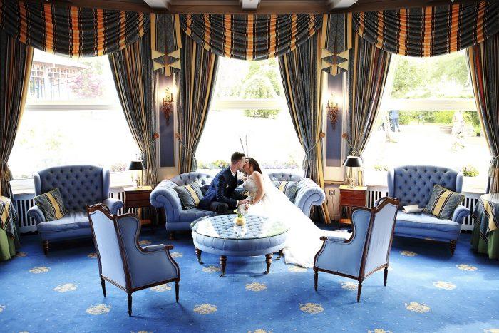 Matrimonio da favola nella Foresta Nera, gli sposi si baciano sul divano nella hall del Parkhotel Adler a Hinterzarten , Germania, fotografia emozionale di Mauri Fotostudio, fotografo della Provincia di Teramo, Abruzzo e Marche, Swiss wedding photographer