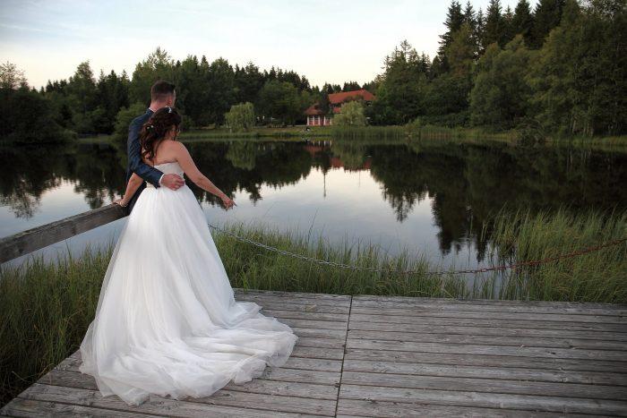 Momenti romantici, gli sposi sul pontile osservano gli abeti della Foresta Nera e le residenze nordiche riflesse nel laghetto dell'incantevole Parco dell'Hotel Adler, Schweizer Hochzeitsfotograf