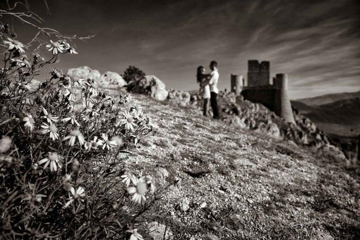 Servizo prematrimoniale a Rocca Calascio spontaneità in bianco e nero tra fiori e castello