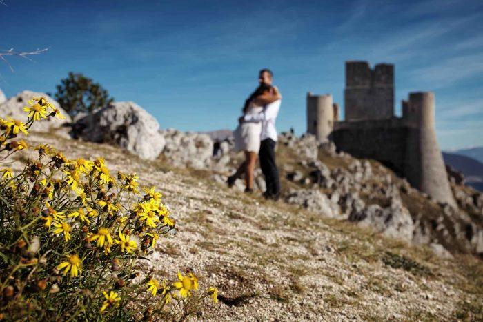 Servizo prematrimoniale a Rocca Calascio abbraccio con fiori gialli in primo piano