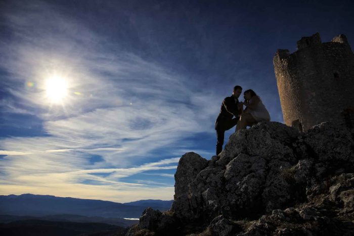 Servizo prematrimoniale a Rocca Calascio seduti sulla roccia in controluce