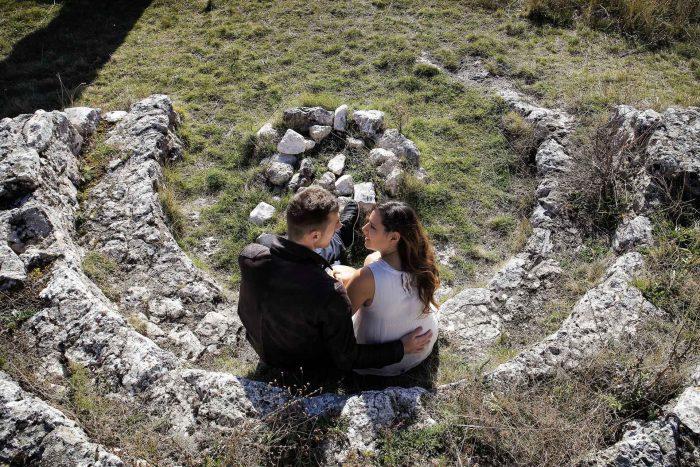 Servizo prematrimoniale a Rocca Calascio coppia avvolta da un semicerchio di pietra